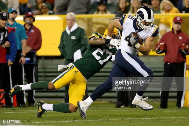 Johnny Mundt of the Los Angeles Rams breaks away from a tackle attempt by Josh Jones of the Green Bay Packers in the fourth quarter during a...