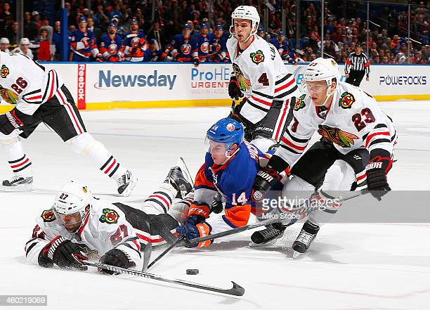 Johnny Oduya and Kris Versteeg of the Chicago Blackhawks skate against Thomas Hickey of the New York Islanders at Nassau Veterans Memorial Coliseum...