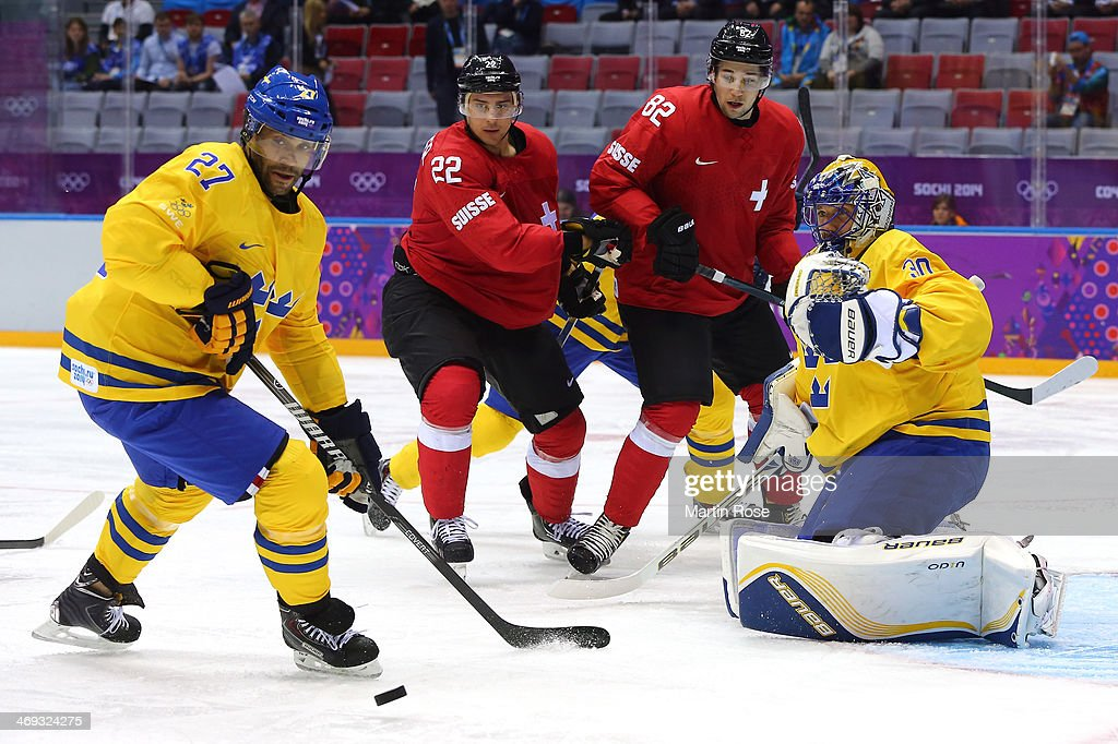 <a gi-track='captionPersonalityLinkClicked' href=/galleries/search?phrase=Johnny+Oduya&family=editorial&specificpeople=3944055 ng-click='$event.stopPropagation()'>Johnny Oduya</a> #27 of Sweden looks to clear the puck against <a gi-track='captionPersonalityLinkClicked' href=/galleries/search?phrase=Nino+Niederreiter&family=editorial&specificpeople=6667732 ng-click='$event.stopPropagation()'>Nino Niederreiter</a> #22 and <a gi-track='captionPersonalityLinkClicked' href=/galleries/search?phrase=Simon+Moser&family=editorial&specificpeople=7727793 ng-click='$event.stopPropagation()'>Simon Moser</a> #82 of Switzerland in the first period during the Men's Ice Hockey Preliminary Round Group C game on day seven of the Sochi 2014 Winter Olympics at Bolshoy Ice Dome on February 14, 2014 in Sochi, Russia.