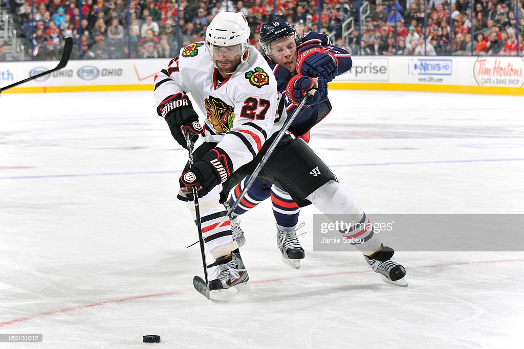 <a gi-track='captionPersonalityLinkClicked' href=/galleries/search?phrase=Johnny+Oduya&family=editorial&specificpeople=3944055 ng-click='$event.stopPropagation()'>Johnny Oduya</a> #27 of the Chicago Blackhawks and <a gi-track='captionPersonalityLinkClicked' href=/galleries/search?phrase=Ryan+Johansen&family=editorial&specificpeople=6698841 ng-click='$event.stopPropagation()'>Ryan Johansen</a> #19 of the Columbus Blue Jackets battle for control of the puck in the third period on January 26, 2013 at Nationwide Arena in Columbus, Ohio. Chicago defeated Columbus 3-2 to start the season 5-0 for the first time in team history.