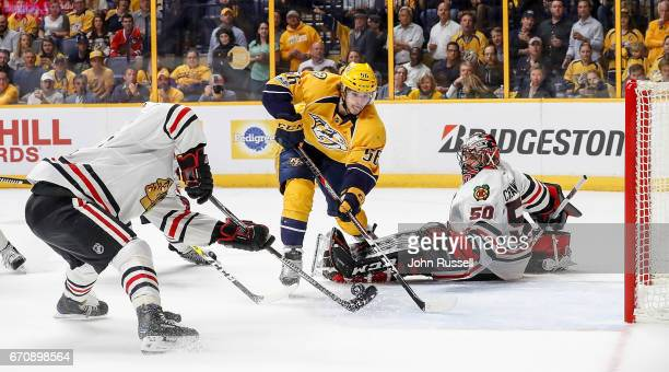 Johnny Oduya of the Chicago Blackhawks defends against Kevin Fiala of the Nashville Predators as Corey Crawford scrambles in Game Four of the Western...