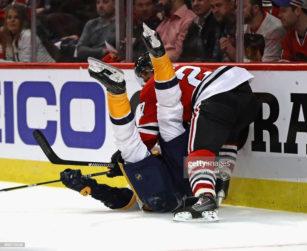 Johnny Oduya #27 of the Chicago Blackhawks dumps Filip Forsberg #9 of the Nashville Predators behind the net in Game One of the Western Conference First Round during the 2017 NHL Stanley Cuo Playoffs at the United Center on April 13, 2017 in Chicago, Illinois.