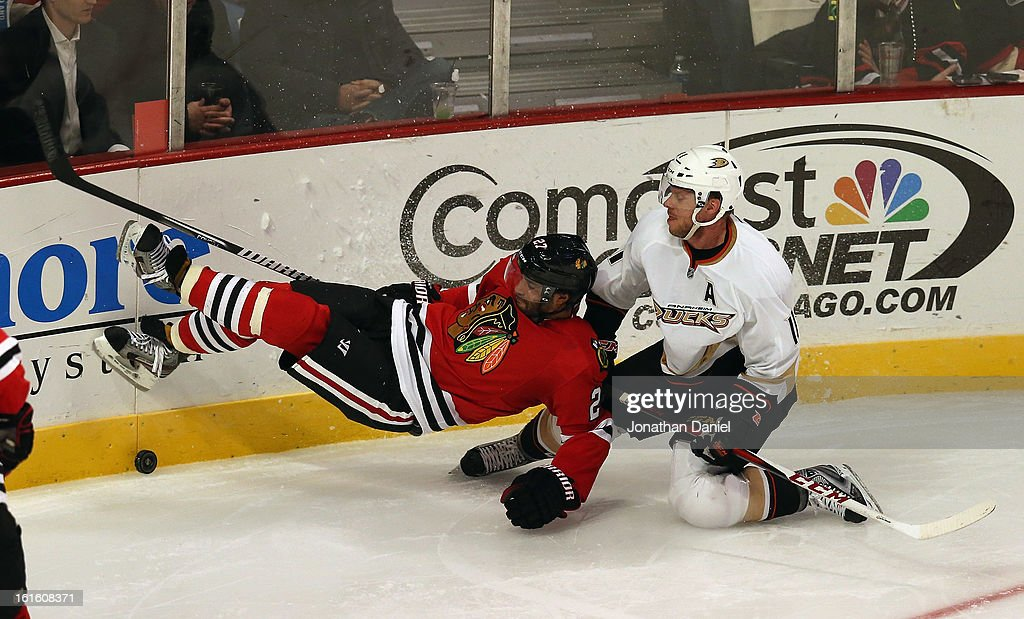 <a gi-track='captionPersonalityLinkClicked' href=/galleries/search?phrase=Johnny+Oduya&family=editorial&specificpeople=3944055 ng-click='$event.stopPropagation()'>Johnny Oduya</a> #27 of the Chicago Blackhawks falls to the ice after being hit by <a gi-track='captionPersonalityLinkClicked' href=/galleries/search?phrase=Saku+Koivu&family=editorial&specificpeople=202253 ng-click='$event.stopPropagation()'>Saku Koivu</a> #11 of the Anaheim Ducks at the United Center on February 12, 2013 in Chicago, Illinois. The Ducks defeated the Blackhawks 3-2 in a shootout.