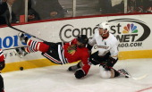 Johnny Oduya of the Chicago Blackhawks falls to the ice after being hit by Saku Koivu of the Anaheim Ducks at the United Center on February 12 2013...