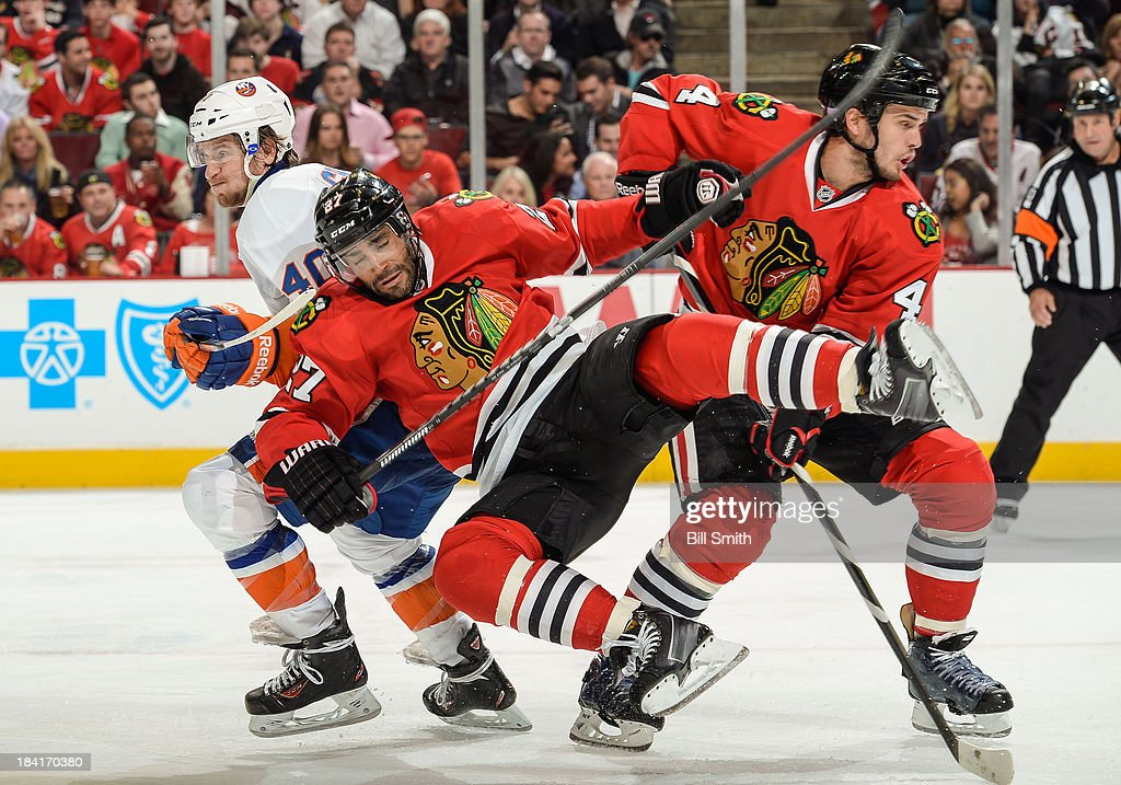 <a gi-track='captionPersonalityLinkClicked' href=/galleries/search?phrase=Johnny+Oduya&family=editorial&specificpeople=3944055 ng-click='$event.stopPropagation()'>Johnny Oduya</a> #27 of the Chicago Blackhawks flies past teammate <a gi-track='captionPersonalityLinkClicked' href=/galleries/search?phrase=Niklas+Hjalmarsson&family=editorial&specificpeople=2006442 ng-click='$event.stopPropagation()'>Niklas Hjalmarsson</a> #4 into <a gi-track='captionPersonalityLinkClicked' href=/galleries/search?phrase=Michael+Grabner&family=editorial&specificpeople=537955 ng-click='$event.stopPropagation()'>Michael Grabner</a> #40 of the New York Islanders during the NHL game on October 11, 2013 at the United Center in Chicago, Illinois.