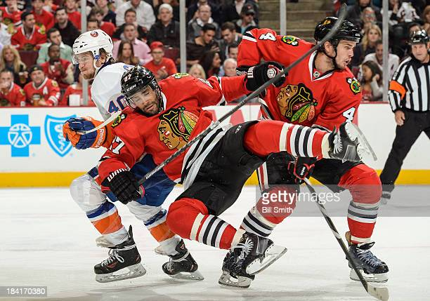 Johnny Oduya of the Chicago Blackhawks flies past teammate Niklas Hjalmarsson into Michael Grabner of the New York Islanders during the NHL game on...