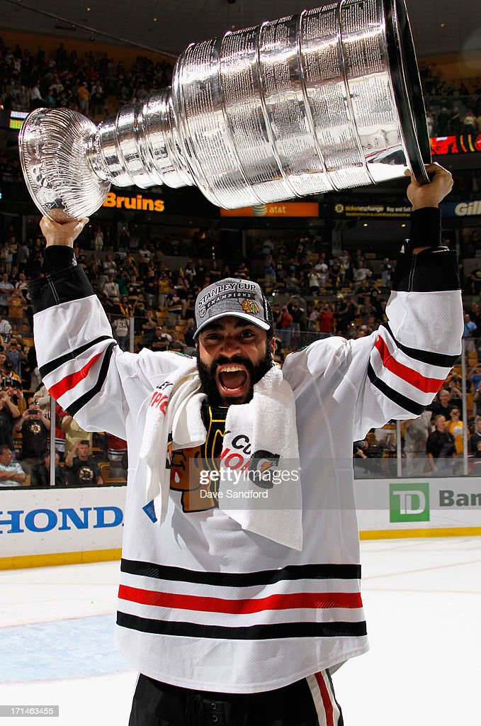 Johnny Oduya #27 of the Chicago Blackhawks hoists the Stanley Cup after his team defeated the Boston Bruins 3-2 in Game Six of the 2013 Stanley Cup Final at TD Garden on June 24, 2013 in Boston, Massachusetts. The Chicago Blackhawks won the series 4-2 to win the Stanley Cup.