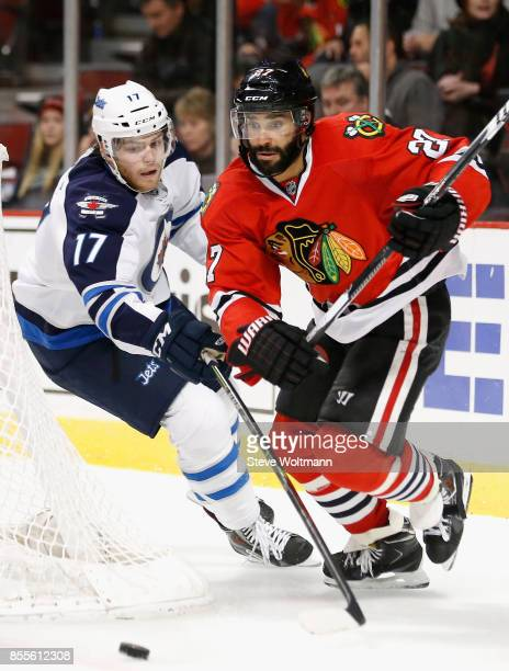 Johnny Oduya of the Chicago Blackhawks plays in a game against Adam Lowry of the Winnipeg Jets at the United Center on December 23 2014 in Chicago...
