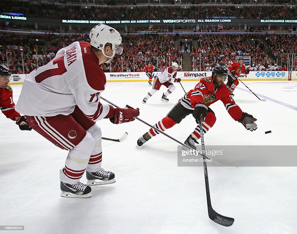 <a gi-track='captionPersonalityLinkClicked' href=/galleries/search?phrase=Johnny+Oduya&family=editorial&specificpeople=3944055 ng-click='$event.stopPropagation()'>Johnny Oduya</a> #27 of the Chicago Blackhawks tries to catch a pass by <a gi-track='captionPersonalityLinkClicked' href=/galleries/search?phrase=Radim+Vrbata&family=editorial&specificpeople=204716 ng-click='$event.stopPropagation()'>Radim Vrbata</a> #17 of the Phoenix Coyotes at the United Center on November 14, 2013 in Chicago, Illinois. The Blackhawks defeated the Coyotes 5-4 in a shootout.