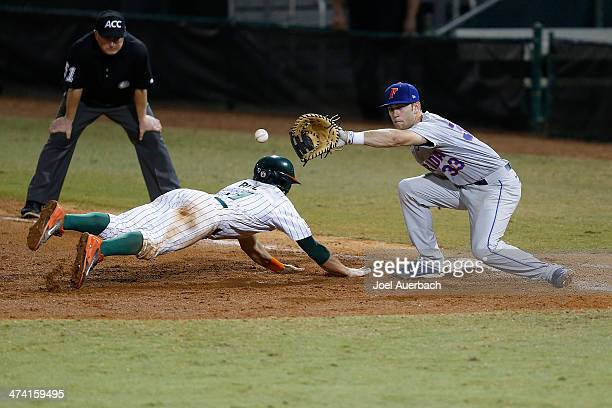Johnny Ruiz of the Miami Hurricanes slides safely back into first base under the tag of Braden Mattson of the Florida Gators on February 21 2014 at...