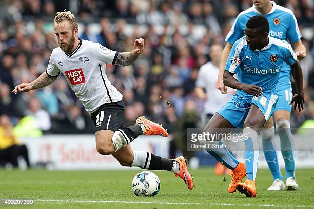 Johnny Russell of Derby County FC trips from a tackle from behind by Bright Enobakhare of Wolverhampton Wanderers FC during the Sky Bet Championship...