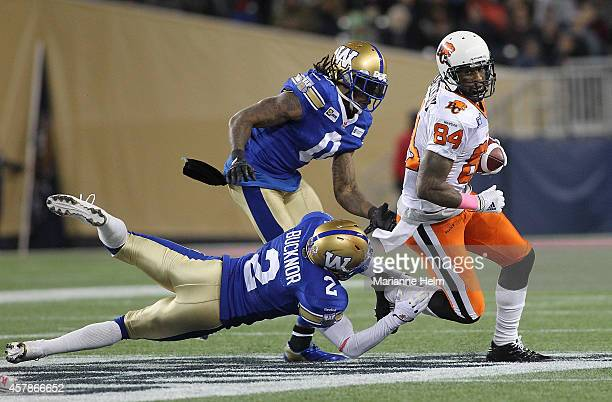Johnny Sears and Matt Bucknor of the Winnipeg Blue Bombers attempt to stop Emmanuel Arceneaux of the BC Lions as he runs for yards in second half...