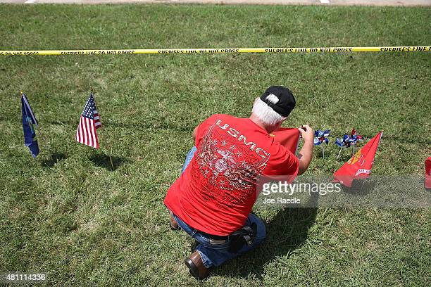 Johnny Stapp whose son just entered the Marine Corps places flags in the memorial in front of the Armed Forces Career Center/National Guard...