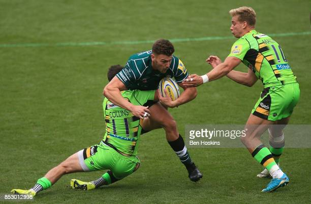 Johnny Williams of London Irish is tackled by Tom Collins and Harry Mallinder of Northampton during the Aviva Premiership match between London Irish...
