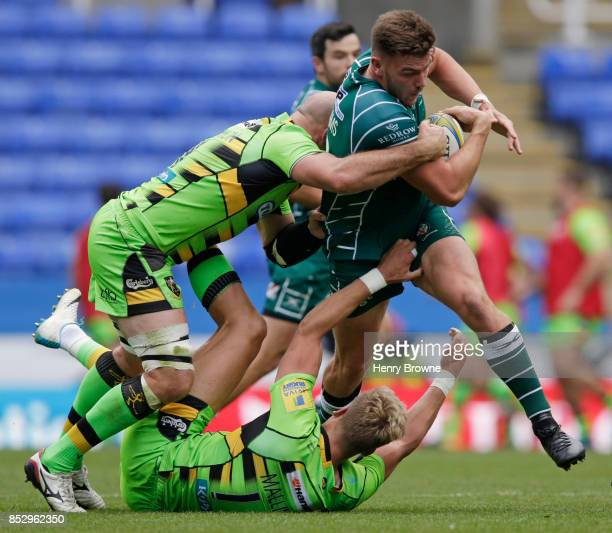 Johnny Williams of London Irish tackled by Sam Dickinson and Harry Mallinder of Northampton Saints during the Aviva Premiership match between London...