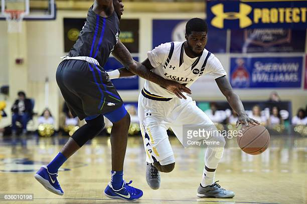 J Johnson of the La Salle Explorers dribbles against RaySean Scott Jr #13 of the Florida Gulf Coast Eagles during the first half at Tom Gola Arena on...