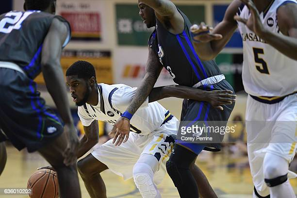 J Johnson of the La Salle Explorers dribbles the ball against RaySean Scott Jr #13 of the Florida Gulf Coast Eagles during the first half at Tom Gola...