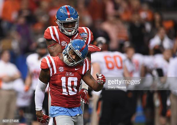 J Johnson of the Mississippi Rebels celebrates sacking the Oklahoma State Cowboys quarterback with his teammate Justin Anderson of the Mississippi...