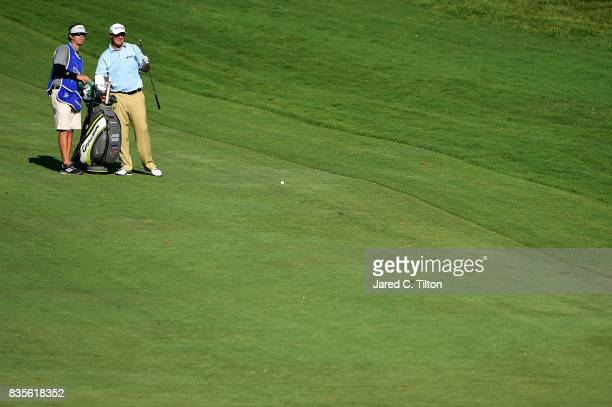 Johnson Wagner and his caddie look on from the 18th fairway during the third round of the Wyndham Championship at Sedgefield Country Club on August...