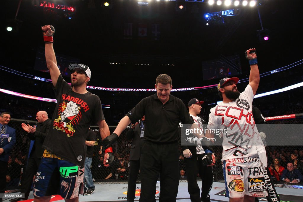Johny Hendricks (R) and Carlos Condit (L) react as the judges' scores are read after their welterweight bout during the UFC 158 event at Bell Centre on March 16, 2013 in Montreal, Quebec, Canada.