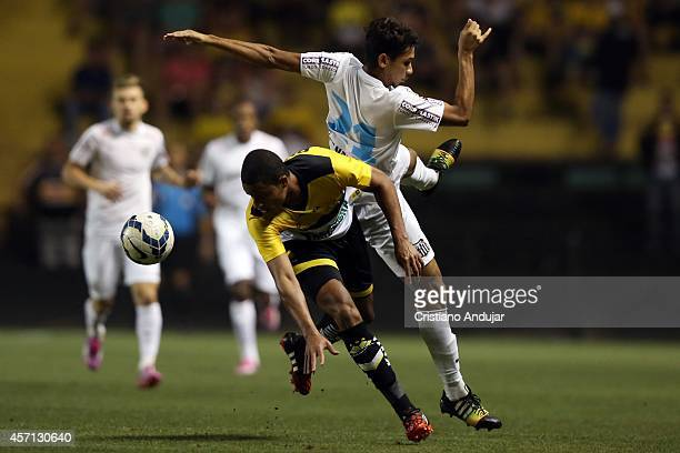 Joilson of Criciuma and Leandrinho of Santos after a header during a match between Criciuma and Santos as part of Campeonato Brasileiro 2014 at...