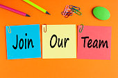 Join our team written on color notes and office supplies. Business Concept. Top view.