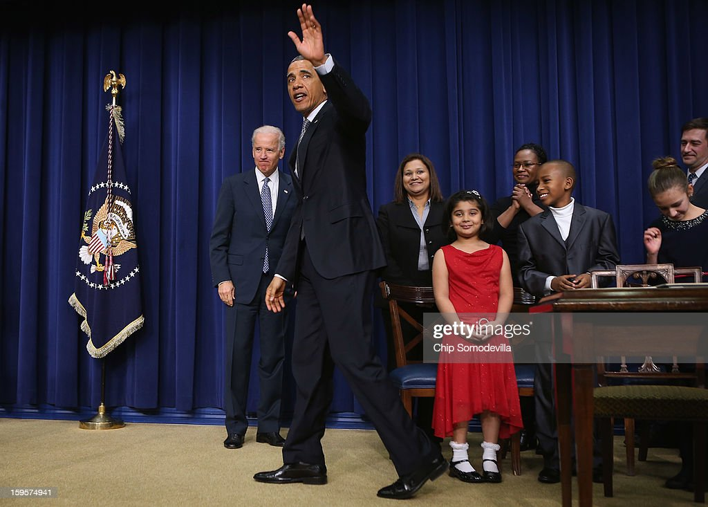 Joined by children who wrote letters to the White House about gun violence, U.S. President Barack Obama (2L) and Vice President Joe Biden (L) wave goodbye after Obama signed executive orders about the administration's new gun law proposals in the Eisenhower Executive Office building January 16, 2013 in Washington, DC. One month after a massacre that left 20 school children and 6 adults dead in Newtown, Connecticut, the president unveiled a package of gun control proposals that include universal background checks and bans on assault weapons and high-capacity magazines.