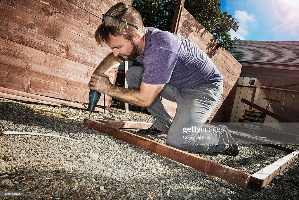 Joiner in backyard drilling wood framework