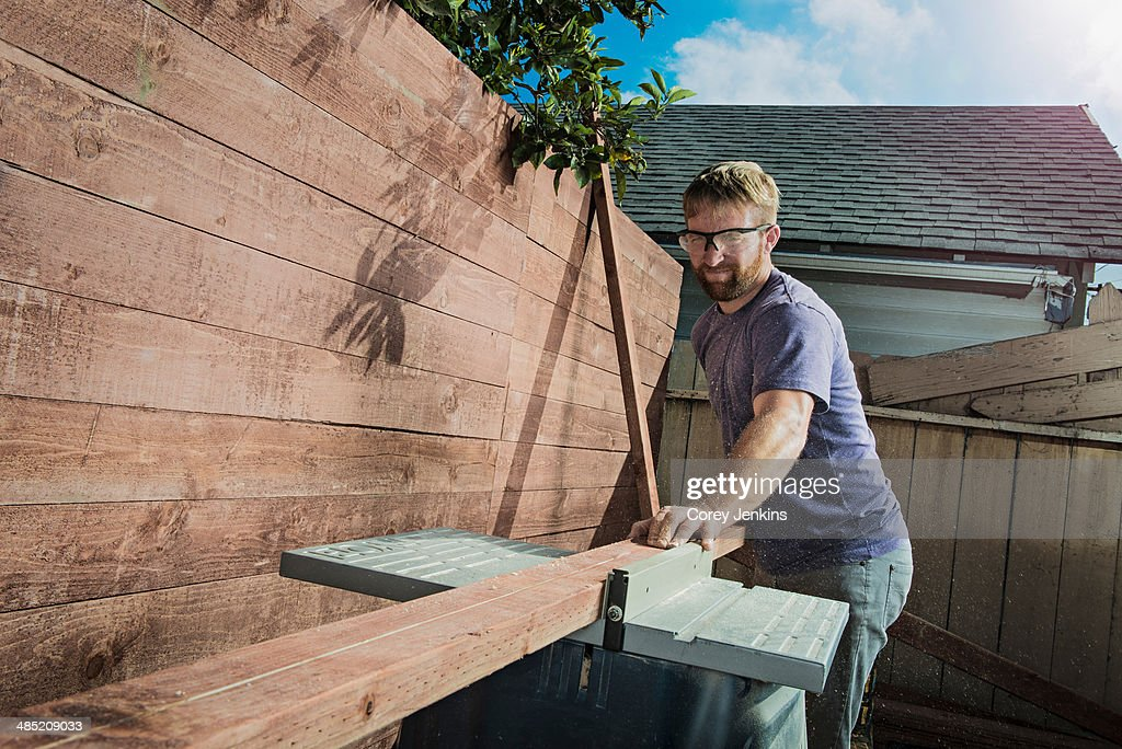 Joiner in backyard measuring planks of wood on workbench