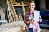 Portrait of happy young woman wearing plaid shirt posing in woodworking shop smiling looking at camera and holding clipboard, copy space