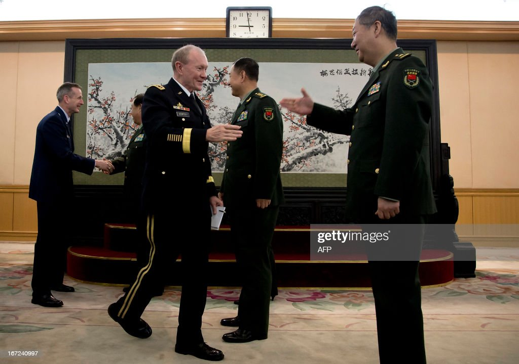 US Joint Chiefs Chairman General Martin Dempsey (front L) shakes hands with Chinese military officers during his visit at the Bayi Building in Beijing on April 23, 2013. Dempsey was expected to discuss concerns over tensions with North Korea, amongst other bilateral items. AFP PHOTO / POOL / Andy Wong
