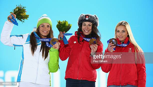 Joint gold medalists Tina Maze of Slovenia and Dominique Gisin of Switzerland and bronze medalist Lara Gut of Switzerland celebrate during the medal...