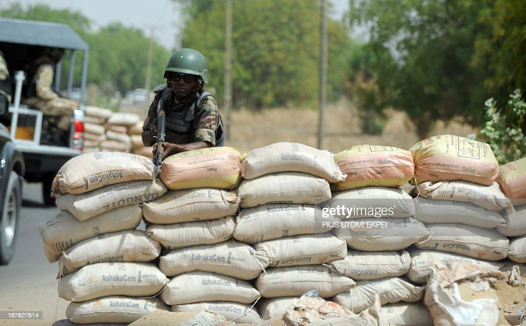 A Joint Military Task Force (JTF) soldier positions his rifle on sand bags on the road in northeastern Nigerian town of Maiduguri, Borno State , on April 30, 2013. Fierce fighting between Nigerian troops and suspected Islamist insurgents, Boko Haram at Baga town in the restive northeastern Nigeria, on April 30, 2013 left dozens of people dead and scores of civilians injured. But the military denied the casualty figures claiming it was exaggerated to smear its image. Meanwhile normalcy has return to the town as residents are going about their normal business.