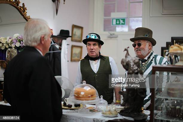Joint proprietor of the Victorian Cafe Chris Fairey serves steampunk enthusiasts during the Asylum Steampunk festival on August 28 2015 in Lincoln...