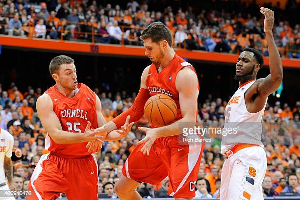 JoJo Fallas of the Cornell Big Red Dave LaMore of the Cornell Big Red and Rakeem Christmas of the Syracuse Orange react to a loose ball during the...