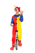 Portrait Of A Clown Juggling With Balls On Unicycle Over White Background
