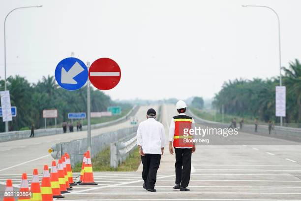 Joko Widodo Indonesia's president right walks with Basuki Hadimuljono Indonesia's minister of public works and housing during the inauguration of the...