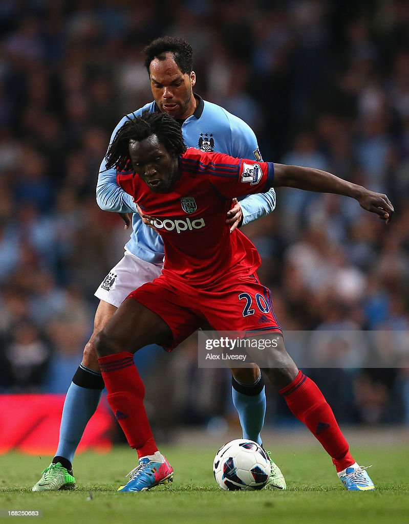 Joleon Lescott of Manchester City competes with Youssouf Mulumbu of West Bromwich Albion during the Barclays Premier League match between Manchester City and West Bromwich Albion at the Etihad Stadium on May 07, 2013 in Manchester, England.