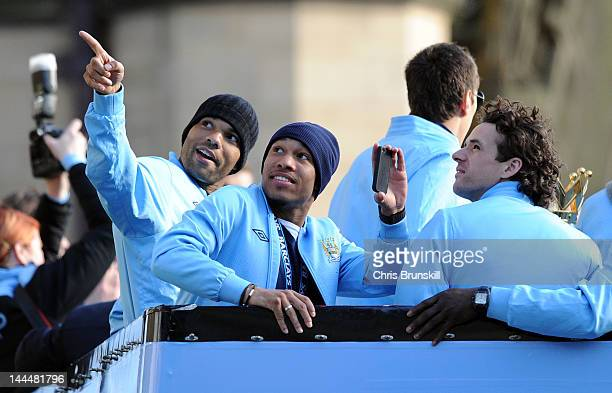 Joleon Lescott of Manchester City points something out to teammates Nigel De Jong and Owen Hargreaves during the victory parade around the streets of...
