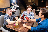 Group of jolly excited young male friends in casual clothing sitting at table in bar and toasting with beer bottles while having fun on Friday