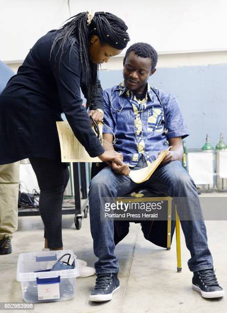 Jolly Ntirumenyerwa of Portland originally from the Democratic Republic of Congo does a medical assesment on Axels Samuntu of Portland who is also...
