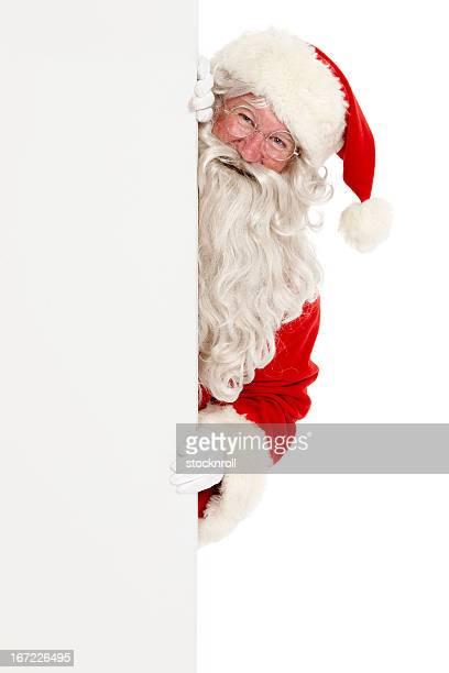 Jolly Santa peeking around a white board.