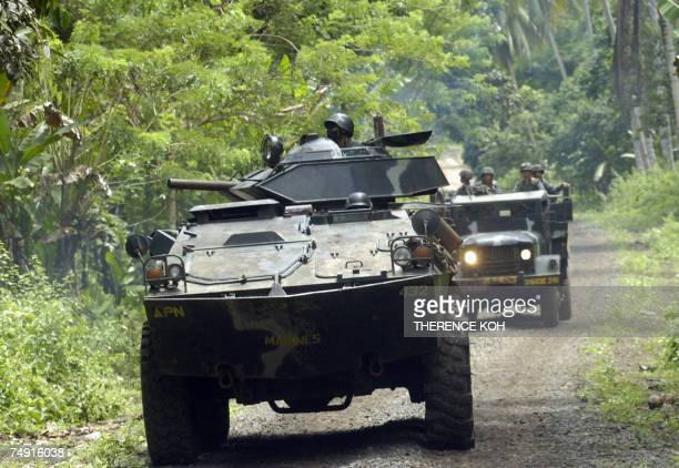 A Philippine armored vehicle and truck loaded with combat troops escort the convoy carrying Admiral Thomas Keating the newly installed Commander of...
