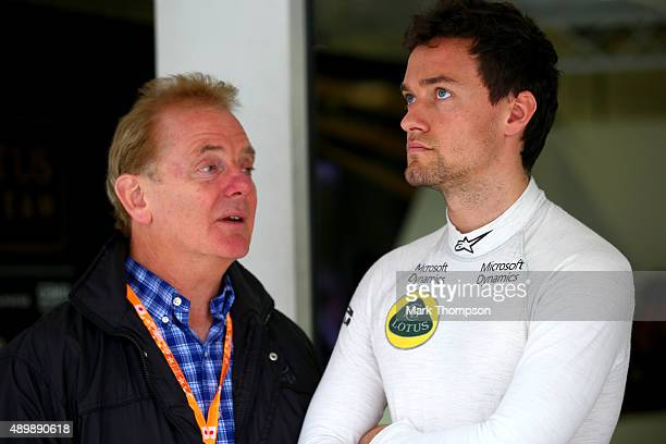 Jolyon Palmer of Great Britain and Lotus speaks with his father Jonathan Palmer outside the team garage during practice for the Formula One Grand...