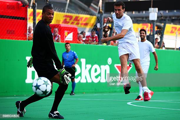 Jolyon Palmer of Great Britain and Renault Sport F1 takes a shot past Dida of Brazil during the Heineken Champions of the Grid Charity football match...