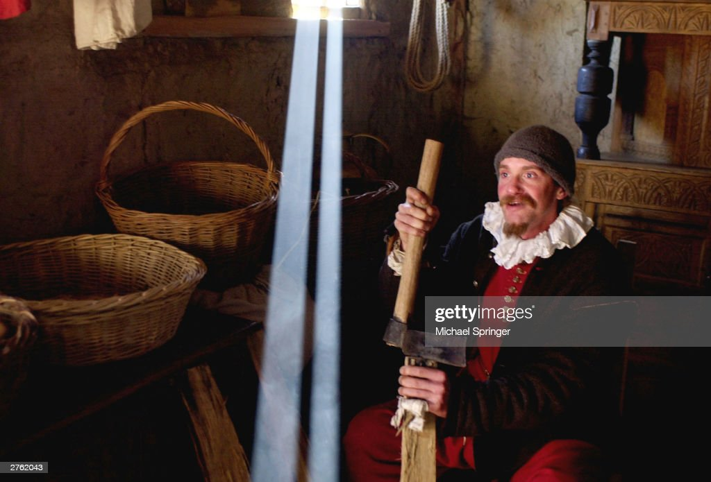 Jolyon Rollins portrays Governor William Bradford leader of the pilgrims splitting wood in his house November 25 2003 at Plimoth Plantation in...