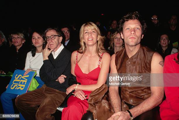 Jon Bon Jovi sits with his wife Dorothea Hurley next to Woody Allen and his girlfriend Soonyi Previn at a Gianni Versace fashion show