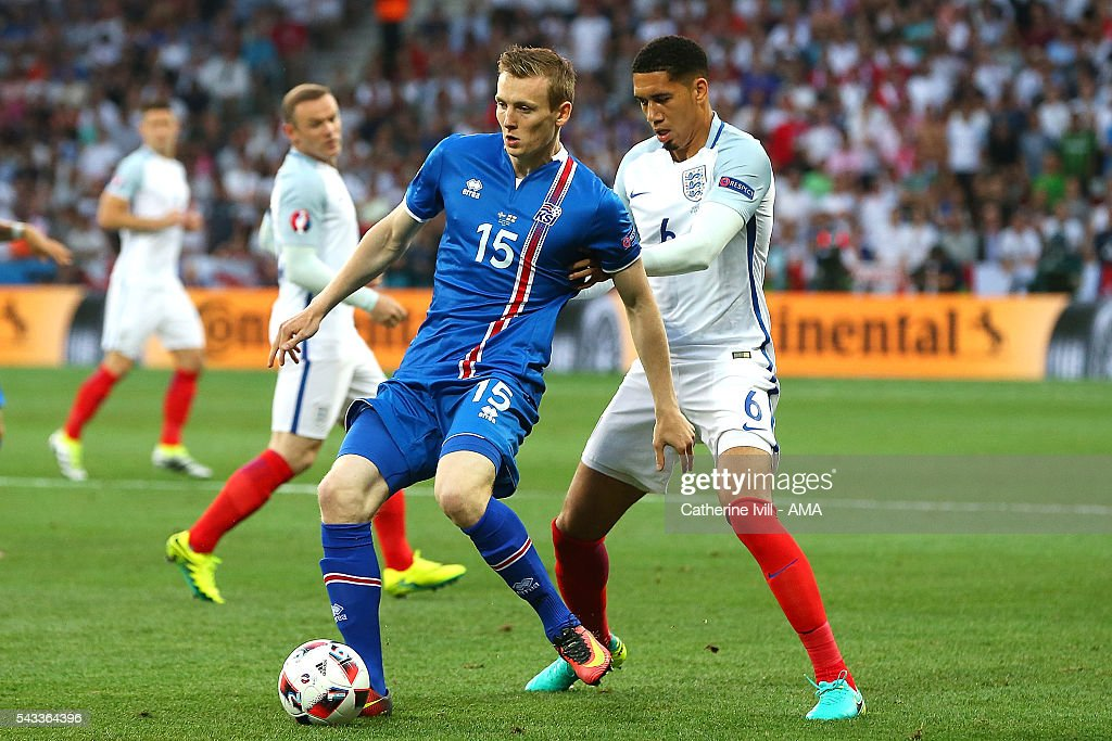 Jon Dadi Bodvarsson of Iceland competes with <a gi-track='captionPersonalityLinkClicked' href=/galleries/search?phrase=Chris+Smalling&family=editorial&specificpeople=5964313 ng-click='$event.stopPropagation()'>Chris Smalling</a> of England during the UEFA Euro 2016 Round of 16 match between England and Iceland at Allianz Riviera Stadium on June 27, 2016 in Nice, France.