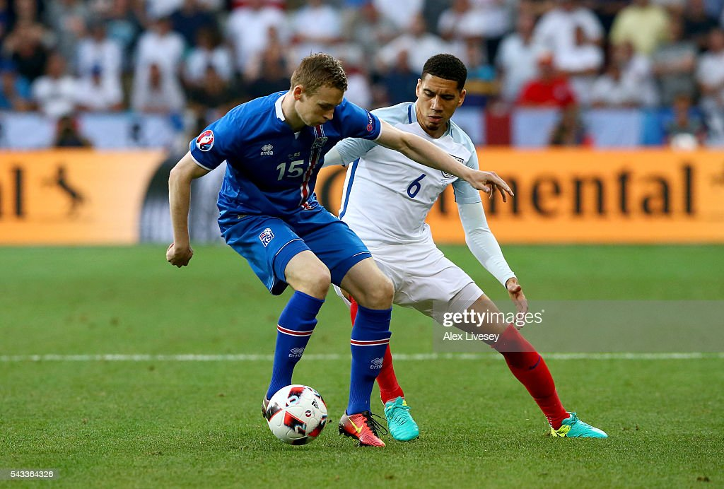 Jon Dadi Bodvarsson of Iceland controls the ball under pressure of <a gi-track='captionPersonalityLinkClicked' href=/galleries/search?phrase=Chris+Smalling&family=editorial&specificpeople=5964313 ng-click='$event.stopPropagation()'>Chris Smalling</a> of England during the UEFA EURO 2016 round of 16 match between England and Iceland at Allianz Riviera Stadium on June 27, 2016 in Nice, France.