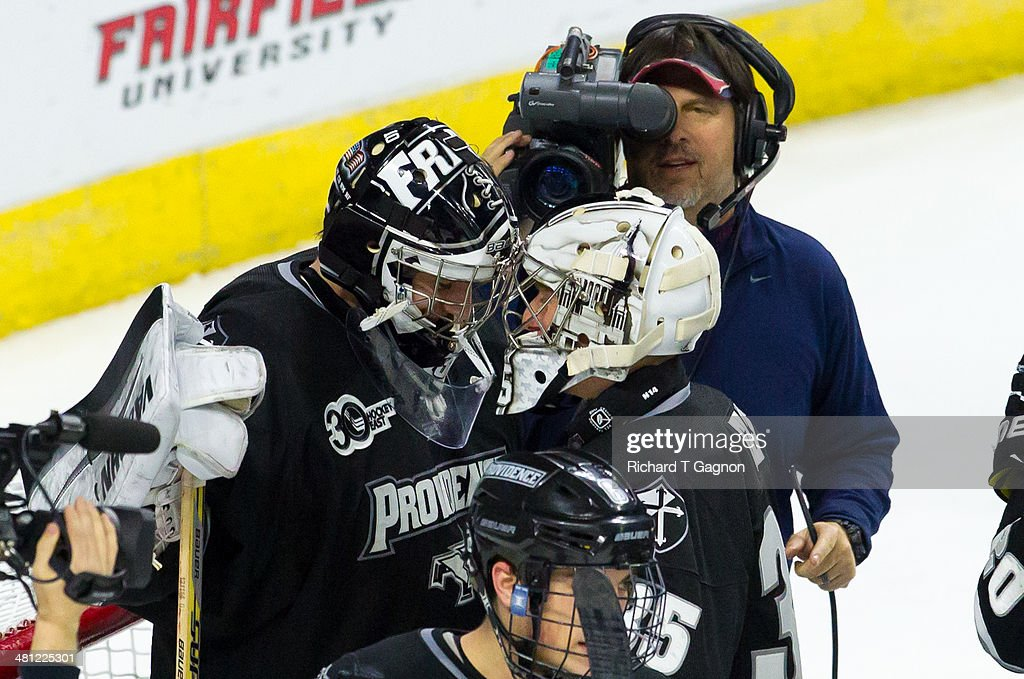 Jon Gillies #32 and Nick Ellis #35 of the Providence College Friars celebrate a victory against the Quinnipiac University Bobcats after the NCAA Division I Men's Ice Hockey East Regional Championship Semifinal at Webster Bank Arena on March 28, 2014 in Bridgeport, Connecticut.